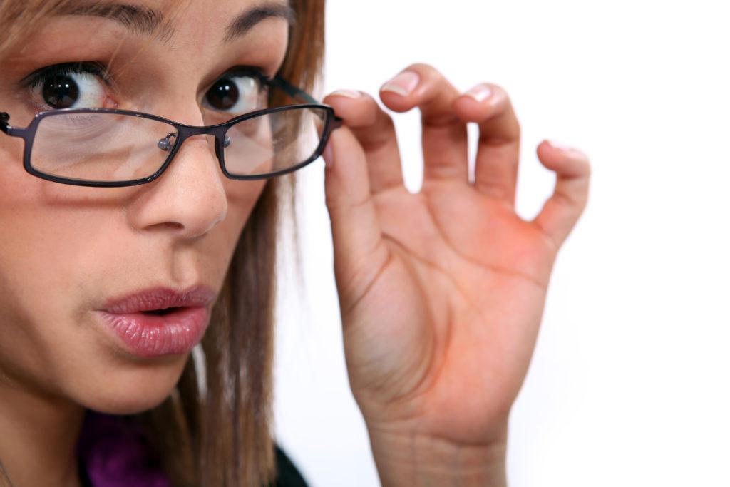 Femme baisant ses lunettes d'un air perplexe