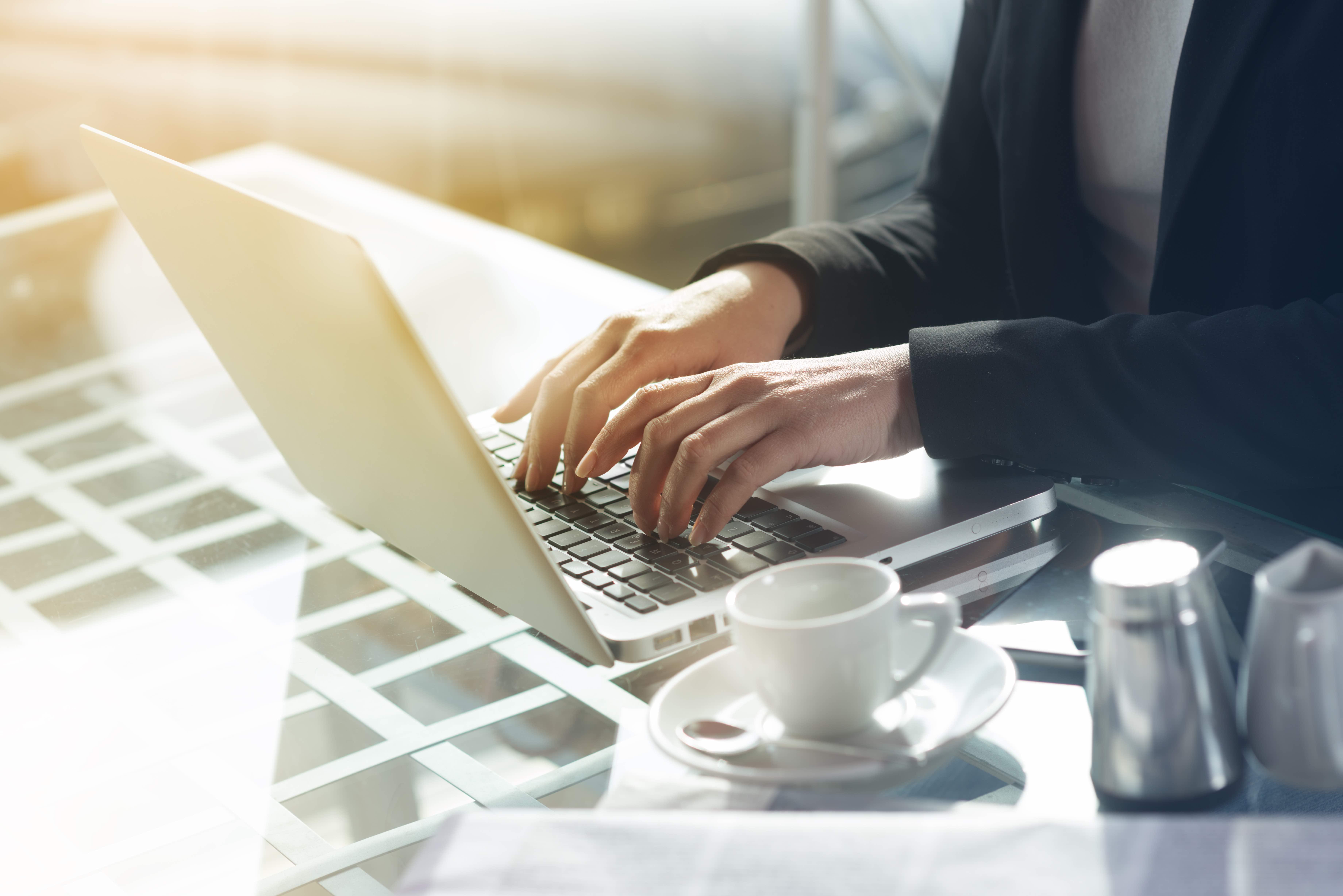 une femme d'affaires travaillant sur son ordinateur avec une vision proche de ses mains sur les communications écrites